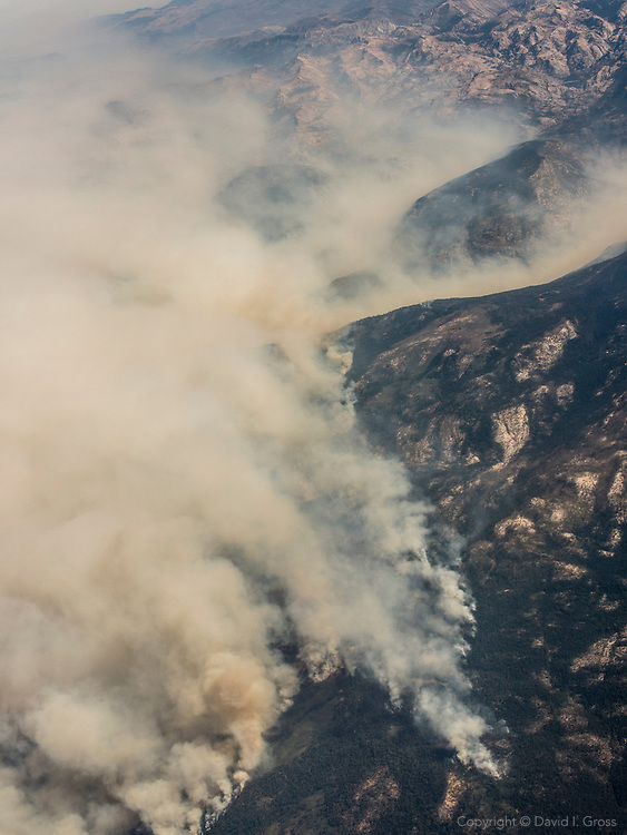 Smoke from the Rim Fire, a huge wildfire outside Yosemite National Park, forms a huge plume over the land as seen from an airplane window.