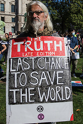 A climate activist stands with a sandwich board in Parliament Square during a Global Climate Strike to demand intersectional climate justice on 24th September 2021 in London, United Kingdom. The Global Climate Strike was organised to highlight the detrimental influences through colonialism, imperialism and exploitation of the Global North on MAPA (Most Affected Peoples and Areas), which have contributed to them now experiencing the worst impacts of the climate crisis, and to call on the Global North to pay reparations to MAPA.