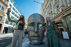 """© Licensed to London News Pictures. 01/06/2021. LONDON, UK. Women view """"Meditation 626"""", 2018, by Seo Young-Deok, made from welded iron chains, which is one of 22 public outdoor sculptures installed as part of this year's Mayfair Sculpture Trail and can be seen around Mayfair 2 to 27 June.  The sculpture trail forms part of the eighth, annual edition of Mayfair Art Weekend which celebrates the rich cultural heritage of Mayfair as one of the most internationally known, thriving art hubs in the world with free exhibitions, tours, talks and site-specific installations available to the public.  Photo credit: Stephen Chung/LNP"""