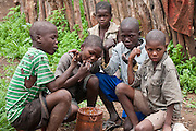 Young boys eat out of an ehoro (traditional wooden bucket) in Okapembambu, a village of the Himba tribespeople  in northwestern Namibia during the rainy season in March. The Himba diet consists of corn meal porridge and sour cow's milk.