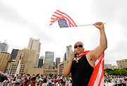 Ivan Romero of Garland Texas holds an American flag while he talks on his cellphone in front of Dallas City Hall during the MegaMarch for Immigration Reform,  May 01, 2010