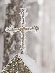 Snowy metal cross on stone, Middle Black Forest, Baden-Wuerttemberg, Germany