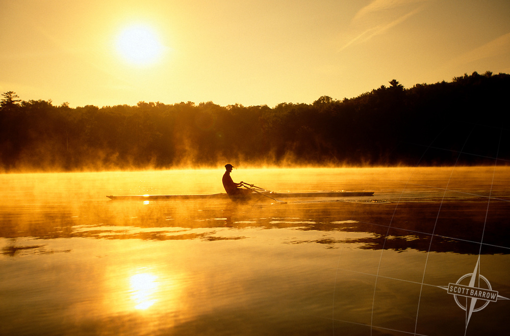 Man rowing a scull on lake.