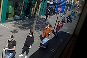 As the UK's Coronavirus death toll during the government's social distancing lockdown, rose by 384 to 33,998, and the R rate of infection is reported to be between 0.7 and 1.0, south Londoners queue for the Post Office on the Walworth Road in Southwark, on 15th May 2020, in London, England.
