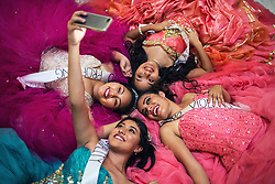 May 13, 2019 - TX, USA - Clockwise from left, Viridiana Sanchez Santos, 16, Brenda Puente, 15, Alexandra Lopez, 18, and Emelyn Macias, 16, all wearing traditional Quinceanera dresses, take a selfie on the floor of the Capitol rotunda after they and other young Latina women held a protest against a Senate bill at the Capitol in July 2017. (Credit Image: © TNS via ZUMA Wire)