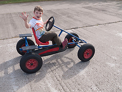 Boy on pedal-operated go-cart