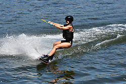 © Licensed to London News Pictures. 25/06/2020.  London UK: Londoners take to the beach at the Royal Victoria Dock in Newham, East London on the hottest day of the year so far. Wakeboarders brave the chilling waters at the man made beach, Photo credit: Steve Poston/LNP