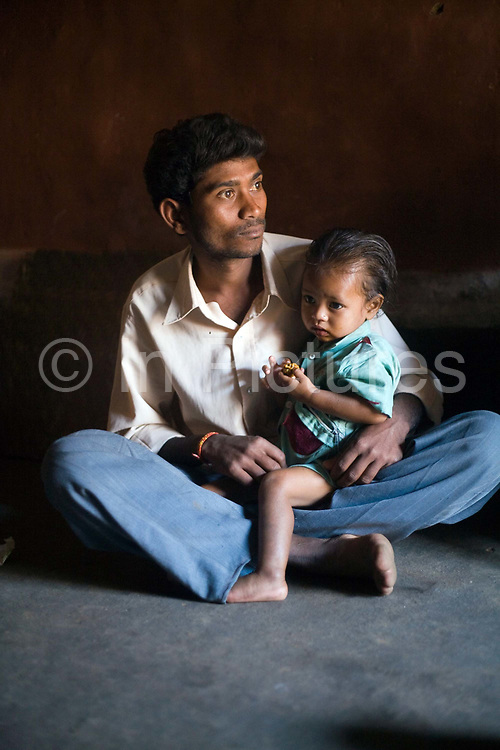 Basati Majhi and his son Ispar, both Dongria Kondh Tribals Kankasarpa village, Orissa, India. The Dongria Kondh are a protected 'Scheduled' Caste of Original (aboriginal) people that practice animism and live a settled rural life. Their deity is a mountain from which a mining company, Vedanta is seeking to extract bauxite which will largely destroy the mountain and the Kondh's traditional way of life.