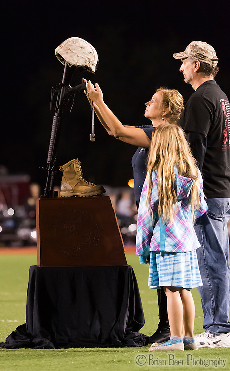 Tom and Patty Schumacher and their daughter Katie, place the dog tags of their fallen son, Victor Drew, on the Battle Field Cross, to honor fallen soldiers before the game  as the Del Oro Golden Eagles varsity football team host the Oak Ridge Trojans, Friday Oct 21, 2016.<br /> photo by Brian Baer
