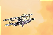 Digitally enhanced rear view image of a biplane in flight