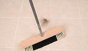 Broom sweeps a dirty floor