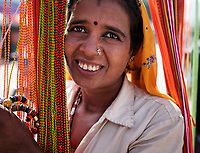 PUSHKAR, INDIA - CIRCA NOVEMBER 2018: Indian woman selling bracelets at the Pushkar Camel Fair grounds. It is one of the world's largest camel fairs. Apart from the buying and selling of livestock, it has become an important tourist destination. The city of Pushkar is a pilgrimage site for Hindus and Sikhs.