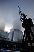 Thick fog over London at the financial district at Canary Wharf making a peaceful yet eerie landscape atmosphere as towers appear and disappear. Modern commercial architecture is releaved through a mist. Here, old cranes still stand where they used to be part of the working docks in this area now called Docklands.