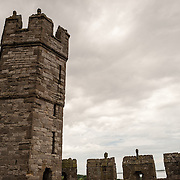 Stormy clouds with ramparts at Caernarfon Castle in northwest Wales. A castle originally stood on the site dating back to the late 11th century, but in the late 13th century King Edward I commissioned a new structure that stands to this day. It has distinctive towers and is one of the best preserved of the series of castles Edward I commissioned.