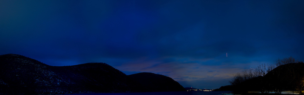View of the Hudson from Cold Spring. Light stripe in sky is from lights of a plane made with long exposure.
