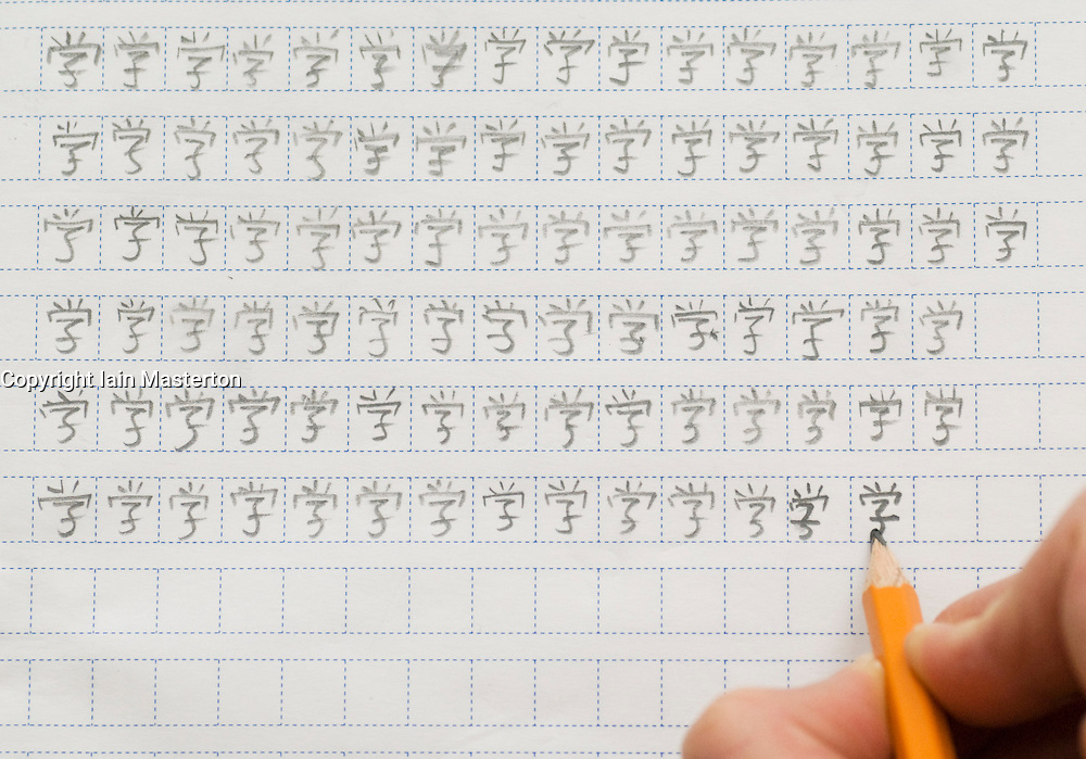 Foreign student of Chinese practicing to write Chinese characters