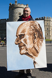 Windsor, UK. 17th April, 2021. Satirical artist Kaya Mar poses in front of Windsor Castle with his painting of Prince Philip on the day of the Duke of Edinburgh's funeral. The funeral of Prince Philip, Queen Elizabeth II's husband, is taking place at St George's Chapel in Windsor Castle, with the ceremony restricted to 30 mourners in accordance with current coronavirus restrictions.