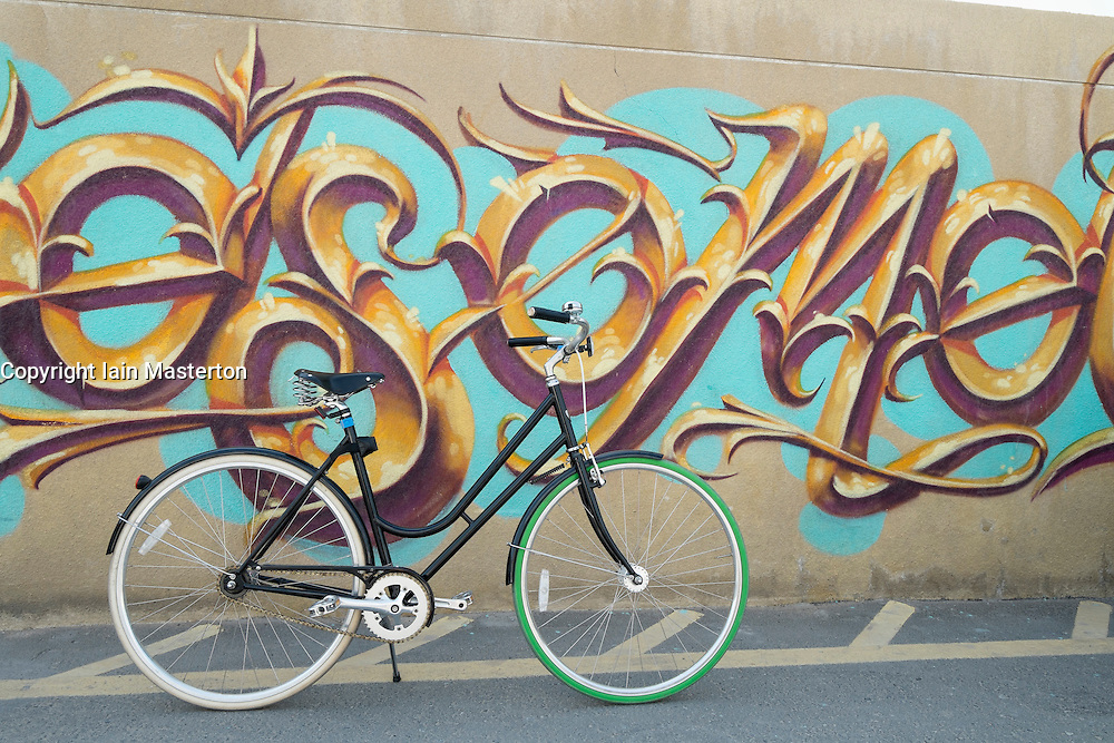 Bicycle and graffiti on wall at Alserkal Avenue art district in Al Quoz Dubai United Arab Emirates
