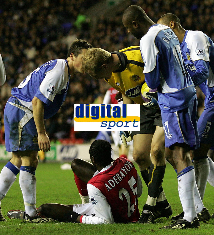 Photo: Paul Thomas.<br /> Wigan Athletic v Arsenal. The Barclays Premiership. 13/12/2006.<br /> <br /> Emmanuel Adebayor (Ground, number 25) of Arsenal is yelled at by Wigan keeper Chris Kirkland (Yellow) after Kirkland was kicked trying to save the ball from Adebayor feet. Adebayor later scored the winner!!