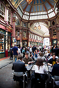 People having lunch outside a restaurant in Leadenhall Market in the City of London. Located in Gracechurch Street, the market dates back to the fourteenth century. There are cheesemongers, butchers and florists. Originally a meat, game and poultry market, it stands on what was the centre of Roman London. Designed in 1881 by Sir Horace Jones.