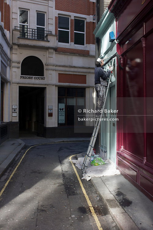 Workman paints exterior of city doorway from the height of an aluminium ladder.