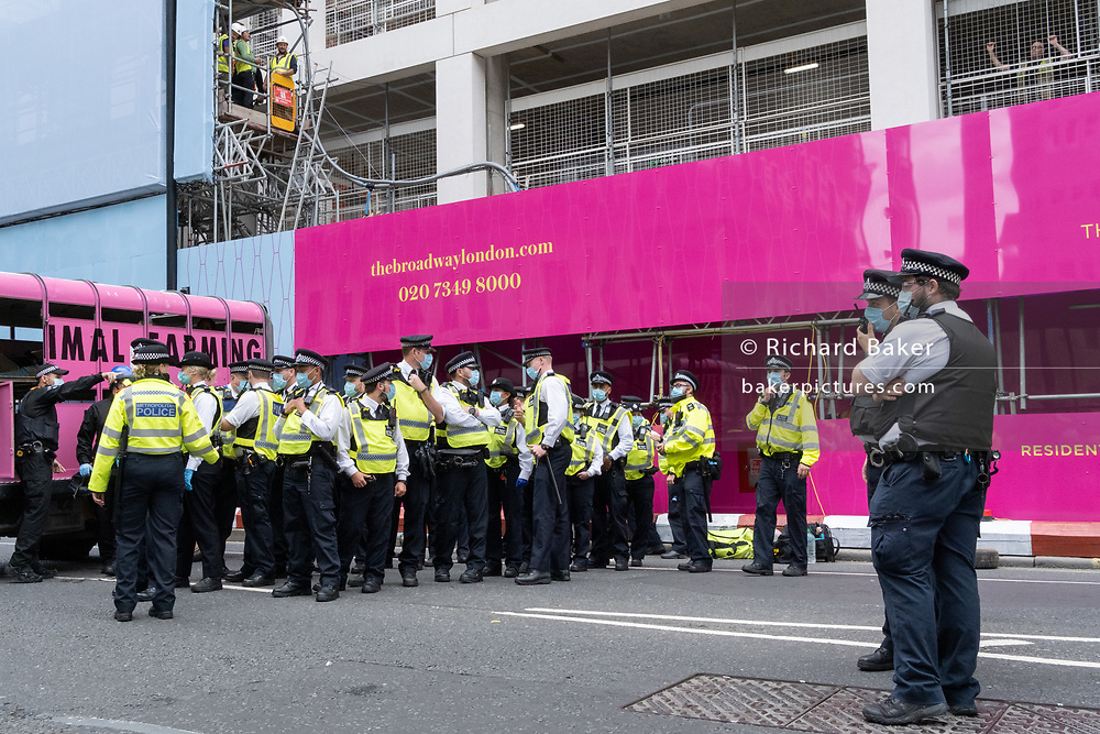 Warched by construction workers, Extinction Rebellion activists are locked inside a live animal transport lorry and Met police officers are briefed before clearing the area and re-open Queen Victoria Street to traffic in Victoria during the Climate Change protests and Coronavirus pandemic, on 3rd September 2020, in London, England.