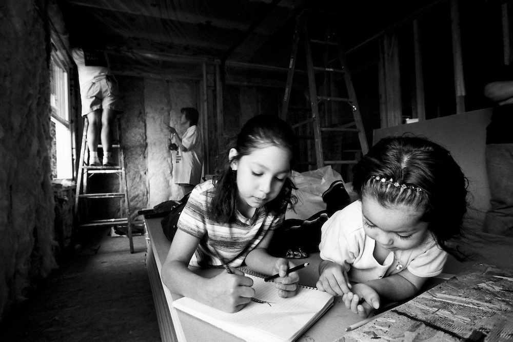 Children of a Habitat family play inside of the house that is being built for their family.