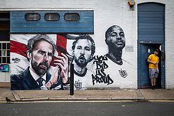 """© Licensed to London News Pictures. 14/07/2021. LONDON, UK.  A man next to a mural by urban street artists MurWalls and commissioned by Sadiq Khan, Mayor of London, which has been unveiled in Vinegar Yard near London Bridge. Featuring the slogan """"You did us proud"""", the artwork celebrates the Engalnd football team's achievement in reaching the final of Euro 2020 and features an image of manager Gareth Southgate, captain Harry Kane and forward Raheem Sterling.  Photo credit: Stephen Chung/LNP"""