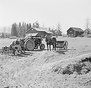 Modern tractor and traditional horse drawn farm machinery in rural farm setting, Finland 1955