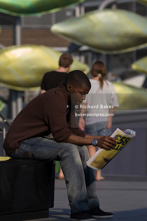 Young black man reads a newspaper on a seat in the Olympic district of Stratford, east London.