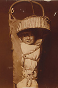 An Apache infant in cradleboard, c1903.  Photograph by Edward Curtis (1868-1952).