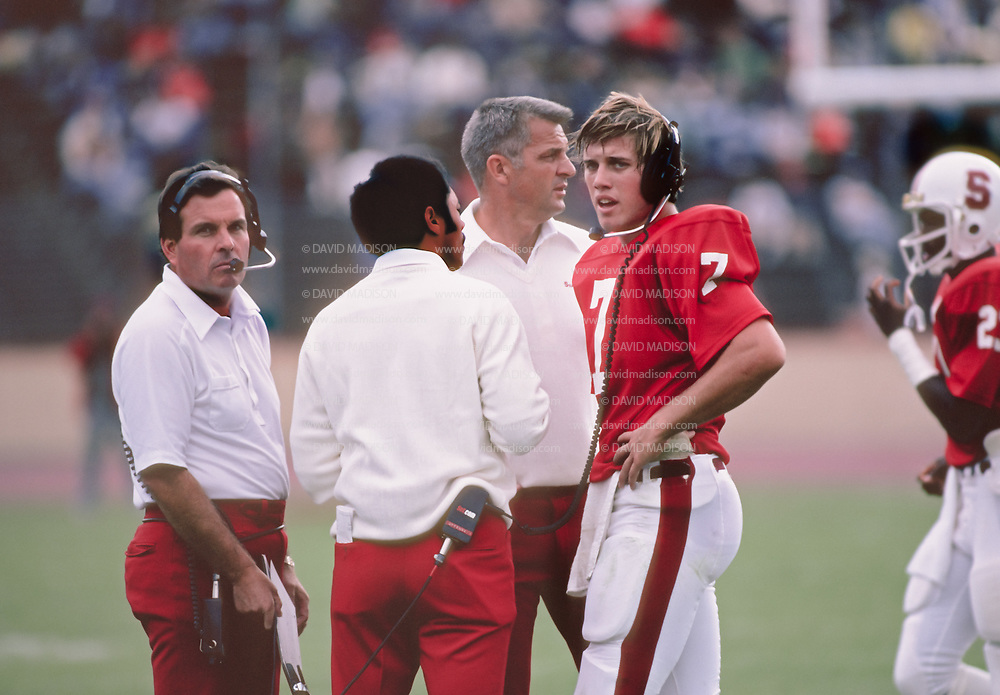 PALO ALTO, CA - OCTOBER 1981:  Quarterback John Elway of Stanford University plays in an NCAA football game against UCLA  on October 10, 1981 at Stanford Stadium in Palo Alto, California.  Visible at left is Coach Dick James, at right without headset is Head Coach Paul Wiggin.  Photo by David Madison   www.davidmadison.com