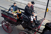 A aerial view of an excited young boy and older tourists being taken around the capital by horse-drawn carriage down Whitehall in Westminster, on 5th June 2019, in London, England.