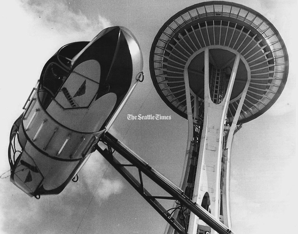 The Roll-O-Plane ride in the Seattle Center Fun Forest appeared to be whirling around the Space Needle in this unusual photograph. The ride was near the south side of the Food Circus in the amusement park. (Bruce McKim / The Seattle Times, 1964)