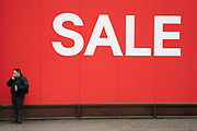 People out shopping on Oxford Street walk past large scale January sale signs in red and white for major high street clothing retail shops on 7th January 2019 in London, United Kingdom. Its time for the Winter sales, and most shops are advertising big reductions in prices. Bargains are available and the shopping streets are busy. Oxford Street is a major road in the West End of London. It is Europes busiest shopping street, with around half a million daily visitors, and has approximately 300 shops.