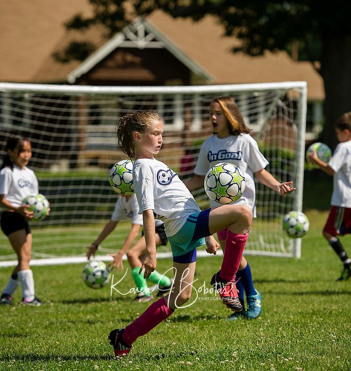 "McKenzie practices her foot skills with the Evangelical Baptist Church ""On Goal"" Soccer Camp at Leavitt Park Thursday morning.  (Karen Bobotas/for the Laconia Daily Sun)"