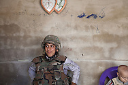 The younger brother of a fighter in the Free Syrian Army tries on his armour and helmet, at a checkpoint between the villages of Meland and Adthar, Idlib province, Syria. 19/11/2012
