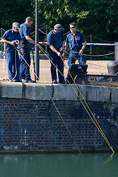Following three reported deaths from drowning on the River thames on Tuesday 23 July as a heatwave grips the UK, a body is recovered by police divers at Shadwell Basin in Wapping, a former riverside cargo dock, now converted to residential use. London, July 24 2019.