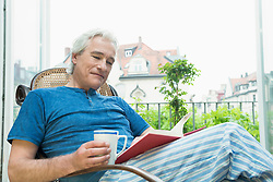 Mature man sitting in rocking chair and reading book