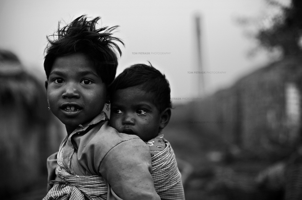 Two children of a family working at a brick kiln in the Sadar area of Patna city. Workers in Bihar's kilns are mainly seasonal migrants from poor households. They are at particular risk of missing polio vaccination rounds and their traveling makes it imperative that they are immunised for fear of spreading the virus. In Bihar state in the May 2006 polio vaccination round there were 173,997 children immunised at brick kilns alone...India is one of only four countries in the world reported to suffer endemic polio. Only 66 new cases of the disease were reported in India in 2005. But in 2006 that figure leapt ten-fold. In September, UN Secretary General Kofi Annan wrote to Indian Prime Minister Manmohan Singh expressing concern at the new polio outbreak. The Indian government, together with partners including Unicef and Rotary International has embarked on a renewed effort to eradicate polio. Overcrowded areas of poor sanitation are particularly susceptible to the virus. Focusing on the poor north Indian states of Uttar Pradesh and Bihar which between them are home to more than 250 million people, Unicef is coordinating the largest public health drive in the world. The task is to vaccinate all children under the age of five during a series of vaccination rounds. Unicef has mobilised thousands of volunteers to administer and supervise the vaccination effort. Unicef has also recruited people with influence to encourage communities to have their children protected against polio. Misinformation, rumours and a frustration with the lack of other health services mean that many households, particularly in Muslim areas, resist vaccination. ..Photo: Tom Pietrasik.Patna, Bihar, India..November 16th 2006