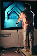 Virtual reality. Appearing to be supported by a high-tech Zimmer frame, computer scientist, John Airey uses a steer-able treadmill to progress on a walk- through tour of a virtual image of a church hall. As he paces on the real treadmill, so he moves towards the altar of the 3-D computer-generated image of the church. Such software packages would be invaluable to architects in judging how their designs may be received by the people who will use them, perhaps well in advance of any real foundations being laid. This photo was taken in the Computer Science Department at the University of North Carolina. Model Released (1990)