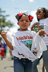 29 August 2015. Lower 9th Ward, New Orleans, Louisiana.<br /> Hurricane Katrina 10th anniversary memorials.  <br /> Cariyan Hurst (6yrs) dances in a second line parade to remember those who perished in the storm.<br /> Photo credit©; Charlie Varley/varleypix.com.