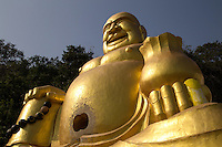 Fat Chinese Buddha at Khao Takiab hill, also known as Monkey Mountain thanks to the large numbers of macaques that live, or rather infest the area. Khao Takiap  projects over the sea for a fabulous view: there is a trail to the top of the mountain, where visitors can clearly admire the scenery of the beach and Hua Hin city.