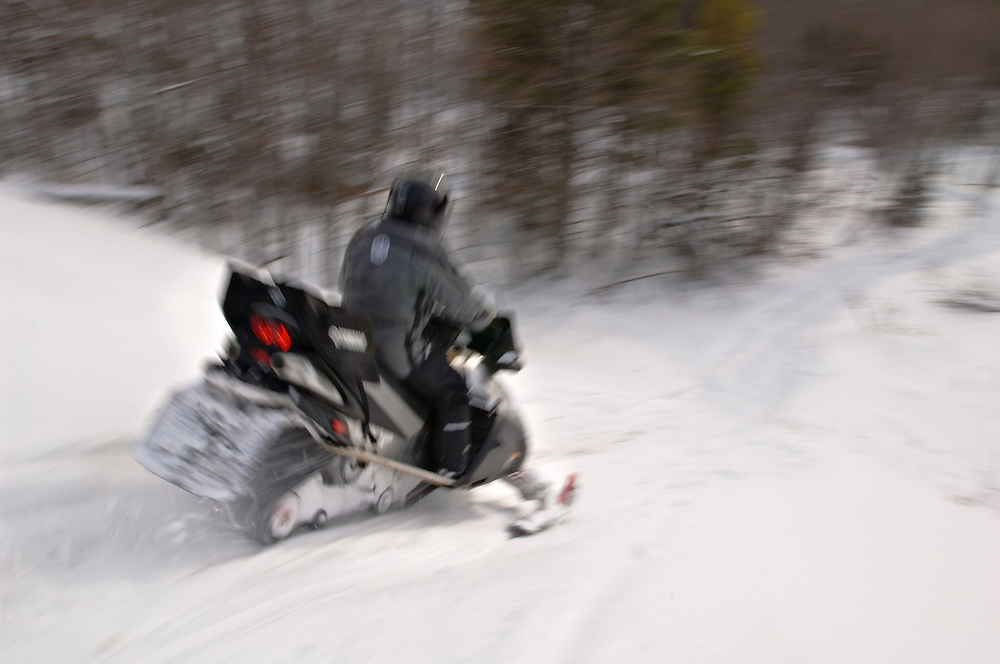 A female client on a Decker Snow-Venture Tours snowmobile tour of the Upper Peninsula goes off-trail to explore some hills and deep powder on the Keweenaw Peninsula.