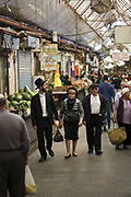 Two Orthodox men and a woman shopping in the Mahane Yahuda Market, Jerusalem, Israel