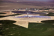 Solar energy electrical generating power plant in the Mojave Desert near Barstow, California. Solar One consists of a circular arrangement of 1, 818 mirrors, each measuring 23x23 feet (7x7 meters). These mirrors focus the sunlight onto a huge central receiver, which sits atop a 300-foot (91 meter) tower. The mirrors are computer controlled to track the path of the sun. Water is pumped through the receiver and heated to a temperature of 960 degrees Fahrenheit. The resultant steam runs a turbine, producing 10 megawatts of power for eight hours a day. (1985).