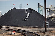 "Kate Clark (l-r),  Eric Ross, Erik Bonnett and Tom Weiss stage a protest with mock wind turbines and a giant ""Renewables Now"" banner on the coal pile at the Valmont Power Plant in Boulder, Colorado on April 27, 2010. The four climate activists claimed the coal mound for over an hour before they were arrested for trespass."