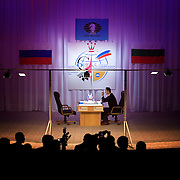 World chess champion Veselin Topalov faces an empty chair during one of the most important chess matches in history. ..Topalov, a Bulgarian ranked first according to Fide, is playing against Kramnik, who is the Classical Chess World Champion, a title established after Garry Kasparov led a breakaway from Fide in 1993. The two grandmasters, both aged 31, are competing for the right to be undisputed world chess champion..Kramnik, a Russian, did not show up for the fifth game and threatened to withdraw from the match after he was accused of cheating and locked out of his private bathroom. .Kramnik had been leading Topalov 3-1 after four games in the 12-game match. But Kramnik boycotted game five, angered by an Appeals Committee decision to lock the private bathrooms for both players and insist that each use a common bathroom for the rest of the match. Topalov was also unhappy with the decision; his manager said it would not prevent Kramnik from cheating since he would still be alone in the lavatory..The match is hosted by FIDE President Kirsan Ilyumzhinov. ..The match beginning September 21 in Elista, the capital of Europe?s only Buddhist nation, will end a 13-year split in the game that has produced rival claims to the title. ..A Buddhist millionaire businessman, Ilyumzhinov acquired his wealth in the economic free-for-all which followed the collapse of the Soviet Union. ..At the age of just over 30, he was elected president in 1993 after promising voters $100 each and a mobile phone for every shepherd. Soon after, he introduced presidential rule, concentrating power in his own hands. ..He denies persistent accusations of corruption, human rights abuses and the suppression of media freedom. When Larisa Yudina, editor of the republic's only opposition newspaper and one of his harshest critics, was murdered in 1998, he strenuously rejected allegations of involvement. ..Mr Ilyumzhinov has been president of the International Chess Federation (FIDE) since 1995 and has been