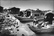 Ethnic Vietnamese fishermen's boats tied up, where fishmongers sell fish nearby, along a road that is slowly being exposed as the waters of Tonle Sap slowly recede at the end of the monsoon, Chong Kneas, Cambodia.