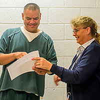Thomas Begay Jr. receives a certificate of completion from Jail Treatment Program Manager Erika Hayes during a graduation luncheon at the McKinley County Adult Detention Center in Gallup Wednesday.